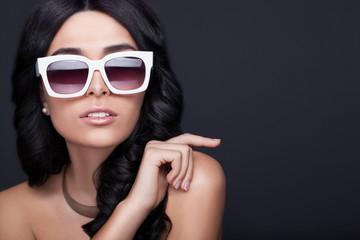 Beautiful woman in white stylish sunglasses