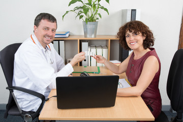 Doctor man sitting with  femmale patient at the desk