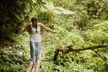 A woman walking carefully across a bamboo bridge in the jungle.