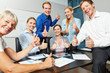 Business Team hält Daumen hoch im Büro
