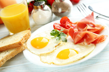 Fried eggs with bacon and toasts on plate on blue wooden table