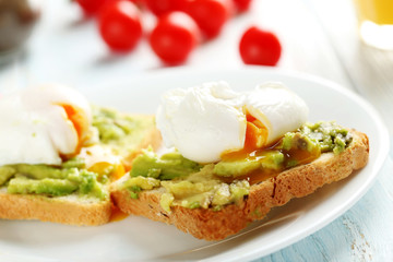 Poached eggs with avocado on toasts on blue wooden table
