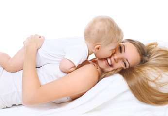 Happy smiling mother and baby playing together on bed
