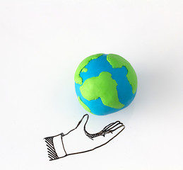 Ecology concept with modelling clay of earth globe on drawing of hand on white background.