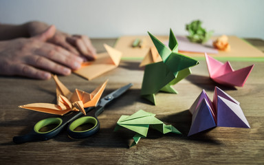 Origami figures, scissors and pencils on wooden table, in the background hands folding colored paper