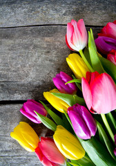 colorful tulips on wooden surface