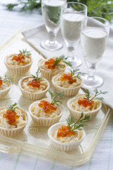 Tartlets with cream cheese and red caviar close up. Snacks with red caviar with aperitif. Light background.
