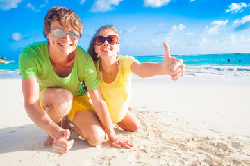 close up of happy young caucasian couple in sunglasses smiling on beach