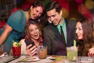 Vier Freunde sehen sich zusammen Urlaubsbilder auf dem Smartphon