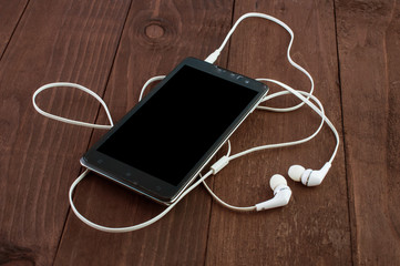 smartphone and headphones on a wooden table