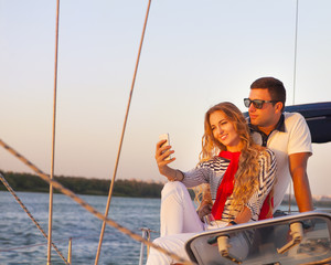 Beautiful couple taking a selfie on a sailing boat at summer