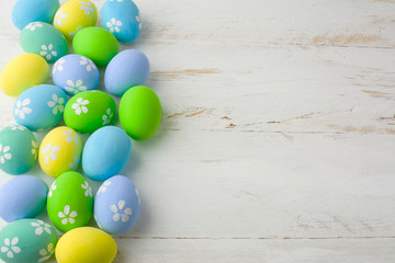 Colored Easter eggs on a wooden white background, copy space