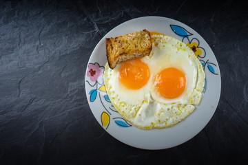 Huevo frito con dos yemas y pan tostado
