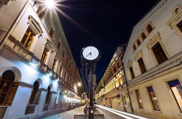 Obraz Antyczny zegar na ulicy Piotrkowskiej w Łodzi wieczorem - fototapety do salonu