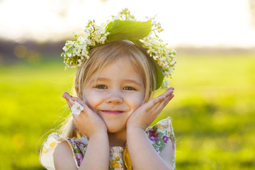Cute little girl with blond hair in a wreath of lily of the vall
