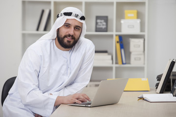 Young Arabic business man working on computer in his office