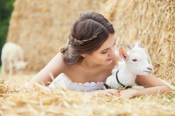 Young woman hugging a small lamb at farm