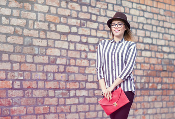 Young attractive student woman wearing hat and glasses holding a bag, brick wall at the background
