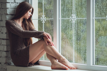Beautiful young woman sitting alone near window with rain drops. Sexy and sad girl. Concept of loneliness