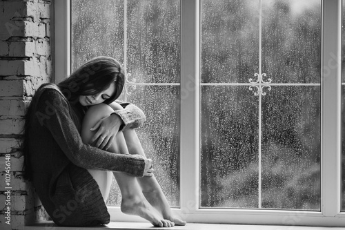 Beautiful young woman sitting alone close to window with rain drops. Sexy and sad girl