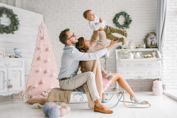 Young happy family holding baby in christmas decor studio