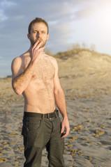 Hombre en actitud chulesca fumando un cigarro sin camiseta