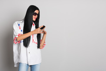 Stylish young woman uses a cell phone