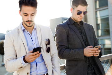 Young businessmen using a mobile phone outdoors.