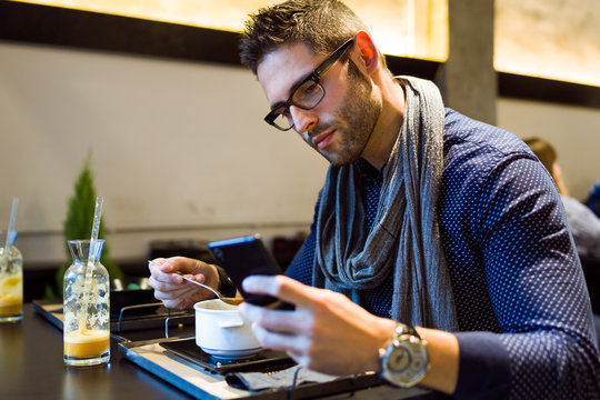 Handsome young man using his mobile phone in restaurant.