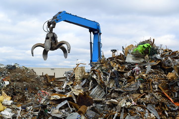 Blue hydraulic Clow Crane used for picking up scrap metal at recycling yard