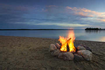 Camp fire on sandy beach, beside lake at sunset. Minnesota, USA