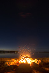 Sparking camp fire beside lake under a starry sky
