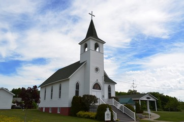 Traditional style architecture Christian church and steeple against a summer sky Wall mural