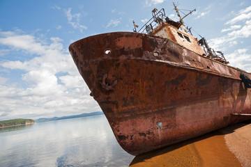 Fotobehang Schip Old fishing vessel on the sea shore