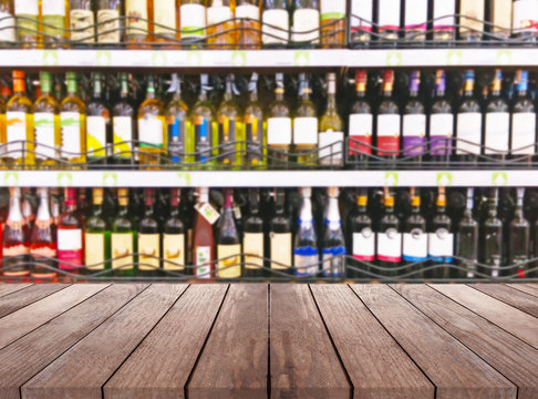 Wood table and wine Liquor bottle on shelf Blurred background