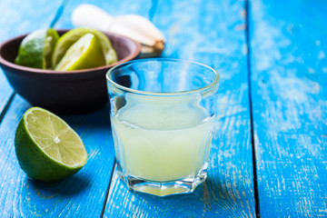 Glass with fresh lime juice on blue wooden background
