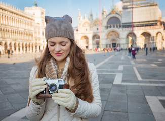 Young woman with retro photo camera standing on Piazza San Marco
