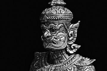 Buddhist stone statue. Giant guardian on black background
