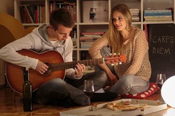Man plays an acoustic guitar at a romantic evening for his girlfrined.