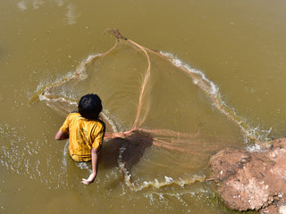 Cambodian girl is fishing on the muddy water
