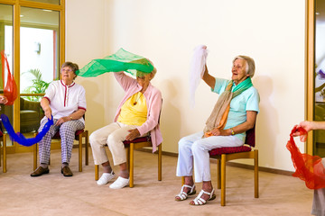 Excited women doing exercises in chairs.