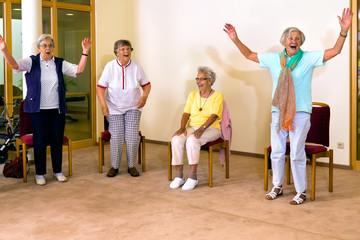 Senior women standing and sitting for exercise.