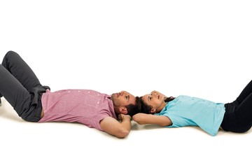 Peaceful young couple laying on floor with hands on their heads