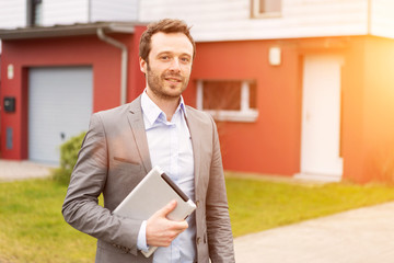 Portrait of a young real estate agent in front of a house