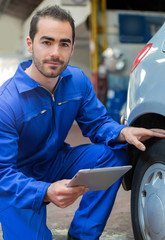 Young attractive mechanic working on a car at the garage