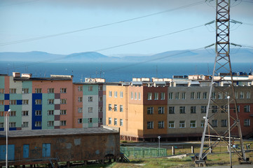 Apartment building block with hilly tundra coast in background