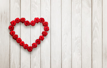 Heart of roses on wooden background with free space for text.