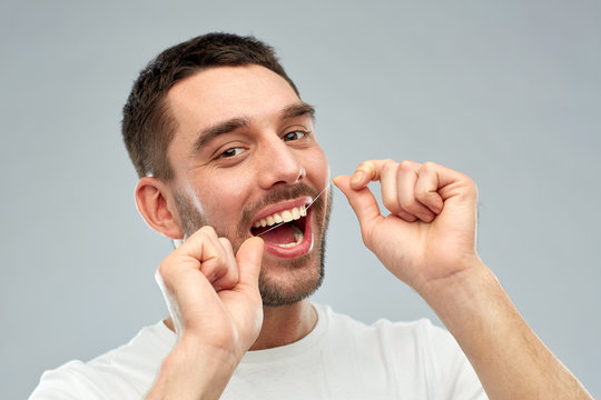 man with dental floss cleaning teeth over gray
