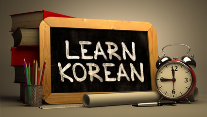 Learn Korean Handwritten on Chalkboard. Time Concept. Composition with Chalkboard and Stack of Books, Alarm Clock and Scrolls on Blurred Background. Toned Image. 3D Render.