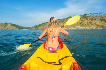Woman exploring calm tropical bay with limestone mountains by kayak.